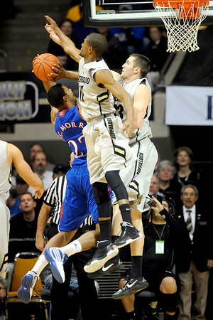 Colorado's Cory Higgins (middle) and Austin Default (right) block Kansas' Marcus Morris (left) during their game at the University of Colorado in Boulder, Colorado January 24, 2011.  CAMERA/Mark Leffingwell