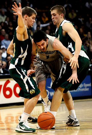 Colorado's Nate Tomlinson (center) crashes into Colorado State's Jesse Carr (left) and Pierce Hornung (right) during their game at the University of Colorado in Boulder, Colorado December 8, 2010.  CAMERA/Mark Leffingwell