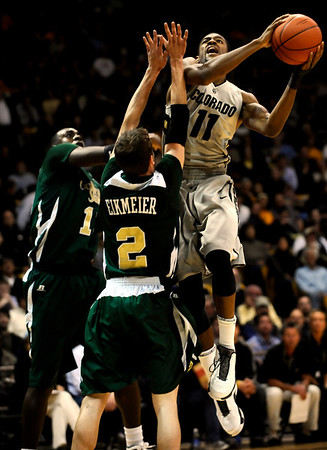 Colorado's Cory Higgins (right) shoots over Colorado State's Andre McFarland (left) and Wes Elkmeier (center) during their game at the University of Colorado in Boulder, Colorado December 8, 2010.  CAMERA/Mark Leffingwell