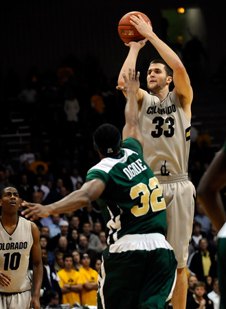 Colorado's Austin Dufault (right) shoots over the head of Colorado State's Andy Ogdie (left) during their game at the University of Colorado in Boulder, Colorado December 8, 2010.  CAMERA/Mark Leffingwell