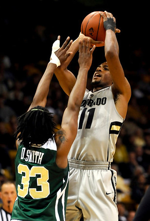 Colorado's Cory Higgins (right) takes a shot over the reach of Colorado State's Will Bell (left) during their game at the University of Colorado in Boulder, Colorado December 8, 2010.  CAMERA/Mark Leffingwell
