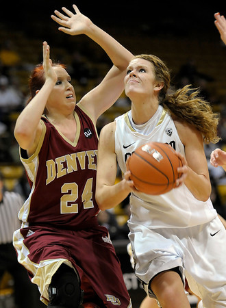 Colorado's Rachel Hargis (right) looks to the basket while being pressured by Denver University's Kaetlyn Murdoch (left) during their basketball game at the University of Colorado in Boulder, Colorado December 8, 2011. CAMERA/MARK LEFFINGWELL