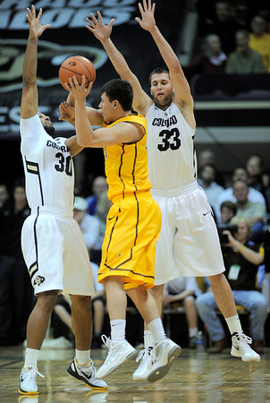 Colorado's Carlon Brown (left) and Austin Dufault (right) block Wyoming's Francisco Cruz (middle) during their basketball game at the University of Colorado in Boulder, Colorado December 9, 2011. CAMERA/MARK LEFFINGWELL