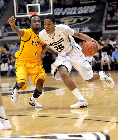 Colorado's Spencer Dinwiddie (right) is guarded by Wyoming's Jaydee Luster (left) during their basketball game at the University of Colorado in Boulder, Colorado December 9, 2011. CAMERA/MARK LEFFINGWELL