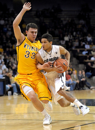 Colorado's Askia Booker (right) bumps Wyoming's Francisco Cruz during their basketball game at the University of Colorado in Boulder, Colorado December 9, 2011. CAMERA/MARK LEFFINGWELL