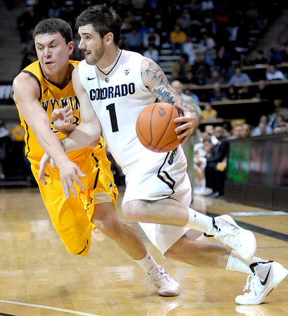 Colorado's Nate Tomlinson (right) pushes in while being guarded by Wyoming's Francisco Cruz (left) during their basketball game at the University of Colorado in Boulder, Colorado December 9, 2011. CAMERA/MARK LEFFINGWELL