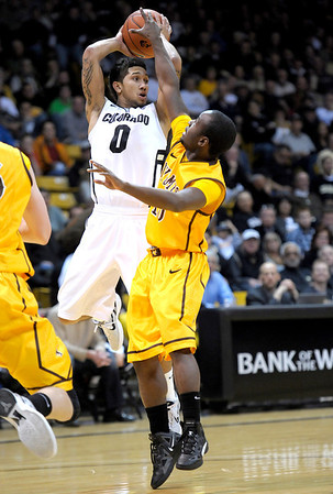 Colorado's Askia Booker (left) looks to pass while being pressured by  Wyoming's Derrious Gilmore (right) during their basketball game at the University of Colorado in Boulder, Colorado December 9, 2011. CAMERA/MARK LEFFINGWELL