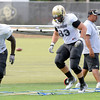 At left Nate Bonsu, 94, leads Will Pericak, 83, and Tony Poremba, 95 through a drill on footwork during the University of Colorado Football practice on Thursday August 25. <br /> Photo by Paul Aiken / The Camera / August 25 2011