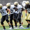 Players follow Tony Poremba, 95, through a footwork drill during the University of Colorado Football practice on Thursday August 25. <br /> Photo by Paul Aiken / The Camera / August 25 2011