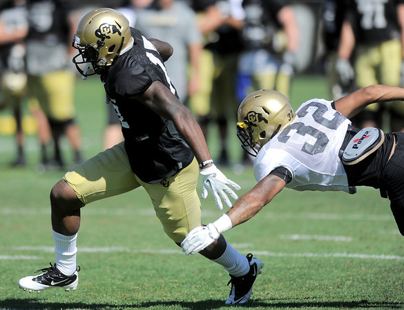 CU's Toney Clemons (left) slips past CU's Paul Vigo during practice at the University of Colorado in Boulder, Colorado August 9, 2011.   CAMERA/Mark Leffingwell