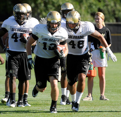 "Liloa Nobriga, 48, chases down Patrick Mahnke, 12, during a ball stripping drill during practice on Sunday morning on the CU Boulder Campus. FOR MORE PHOTOS AND VIDEO INTERVIEWS FROM PRACTICE GO TO  <a href=""http://WWW.DAILYCAMERA.COM"">http://WWW.DAILYCAMERA.COM</a><br /> Photo by Paul Aiken  August 7, 2011."