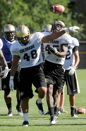 "Lowell Williams, 45, knocks the ball from Liloa Nobriga in a stripping drill during practice on Sunday morning on the CU Boulder Campus. For more photos and video interviews from practice go to  <a href=""http://www.dailycamera.com"">http://www.dailycamera.com</a><br /> Photo by Paul Aiken  August 7, 2011."