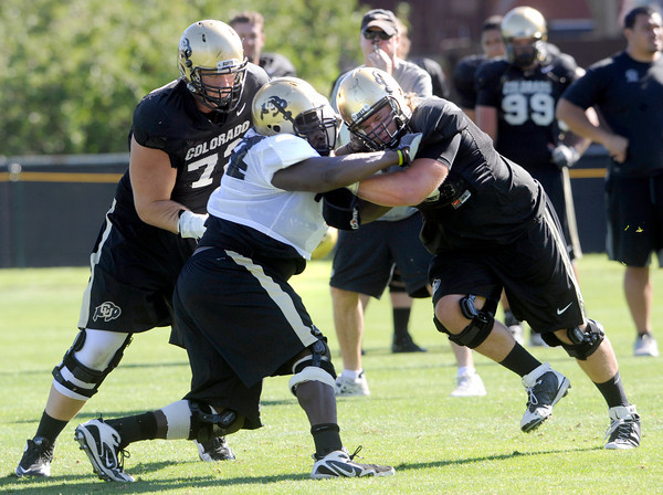 """Nate Bosu, 94, gets caught between Ryan Miller, 73, left and Gus Handler, 76 during practice on Sunday morning on the CU Boulder Campus. FOR MORE PHOTOS AND VIDEO INTERVIEWS FROM PRACTICE GO TO  <a href=""""http://WWW.DAILYCAMERA.COM"""">http://WWW.DAILYCAMERA.COM</a><br /> Photo by Paul Aiken  August 7, 2011."""