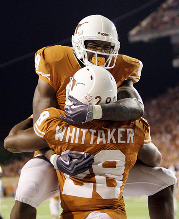 Texas' Fozzy Whittaker (28) celebrates with teammate Malcolm Williams (9) after he scored a touchdown against Colorado  during the fourth quarter of their NCAA college football game in Austin, Texas, Saturday, Oct. 10, 2009. Texas won 38-14. (AP Photo/Eric Gay)