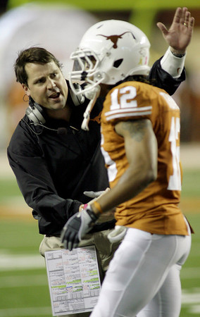 Texas defensive coordinator Will Muschamp, left, congratulates safety Earl Thomas shortly after he grabbed a Colorado pass and returned it 92 yards for a touchdown during the third quarter of their NCAA college football game Saturday, Oct. 10, 2009, in Austin, Texas. Texas won  38-14.  (AP Photo/Harry Cabluck)