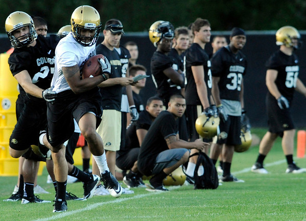 University of Colorado tight-end DaVaughn Thornton, at front, tries to shake a tackle from safety Vince Ewing during the second Buff's football practice on Friday, Aug. 6, at the University of Colorado practice field in Boulder.<br /> Jeremy Papasso/ Camera