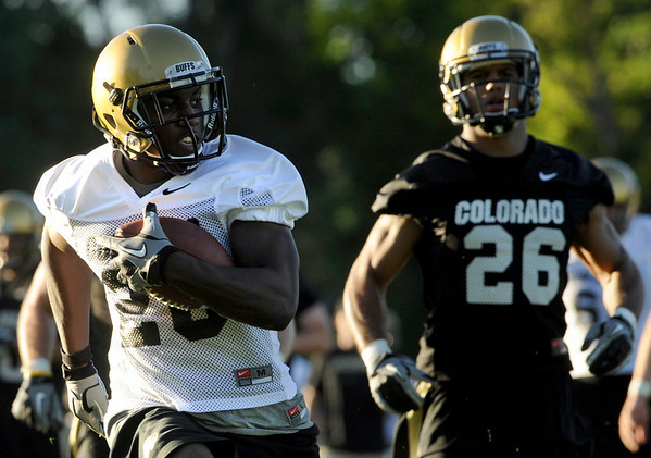 University of Colorado tailback Brian Lockridge rushes past safety Ray Polk during the second Buff's football practice on Friday, Aug. 6, at the University of Colorado practice field in Boulder.<br /> Jeremy Papasso/ Camera