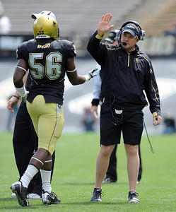 CU assistant coach, Ken Riddle, has a high five for Derrick Webb during the Spring game on Saturday. Cliff Grassmick / April 10, 2010