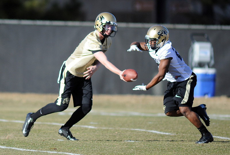 "CU quarterback, Shane Dillon, hands off to Tony Jones at the first Spring football practice on Thursday.<br /> For more photos of practice, go to  <a href=""http://www.dailycamera.com"">http://www.dailycamera.com</a>.<br /> Cliff Grassmick  / March 6, 2013"