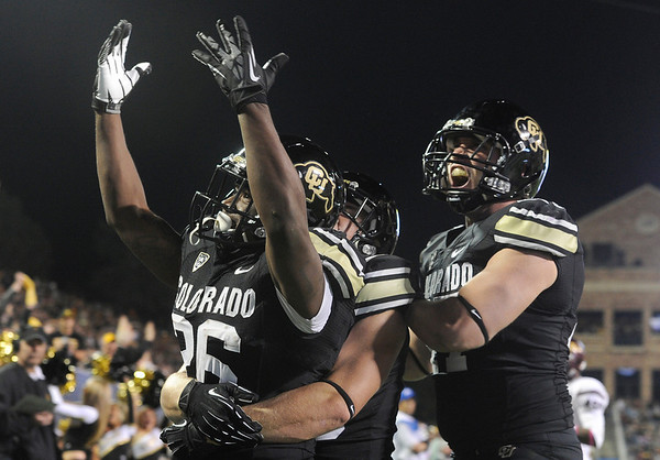 "University of Colorado's Tony Jones, left, is congratulated by teammates Kyle Slavin and Nick Kasa, at right, after scoring a touchdown during a game against Arizona State on Thursday, Oct. 11, at Folsom Field in Boulder. Fore more photos of the game go to  <a href=""http://www.dailycamera.com"">http://www.dailycamera.com</a><br /> Jeremy Papasso/ Camera"