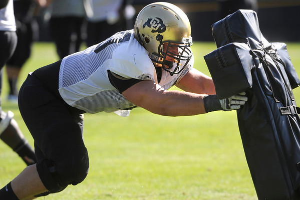 """Eric Richter, 70 works against a sled during the University of Colorado football team practice on Monday.<br /> Photo by Paul Aiken  August 8, 2011.<br /> FOR MORE PHOTOS AND VIDEO INTERVIEWS FROM THE PRACTICE GO TO  <a href=""""http://WWW.DAILYCAMERA.COM"""">http://WWW.DAILYCAMERA.COM</a> OR BUFFZONE.COM"""