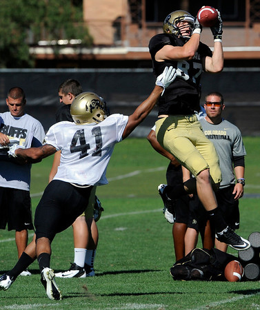 "Tyler McCulloch, 87, tries to pull in a pass over Terrel Smith, 41, during the University of Colorado football team practice on Monday.<br /> Photo by Paul Aiken  August 8, 2011.<br /> FOR MORE PHOTOS AND VIDEO INTERVIEWS FROM THE PRACTICE GO TO  <a href=""http://WWW.DAILYCAMERA.COM"">http://WWW.DAILYCAMERA.COM</a> OR BUFFZONE.COM"