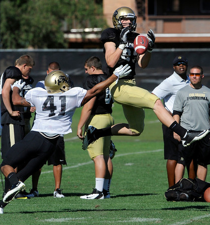 """Tyler McCulloch, 87, tries to pull in a pass over Terrel Smith, 41, during the University of Colorado football team practice on Monday.<br /> Photo by Paul Aiken  August 8, 2011.<br /> FOR MORE PHOTOS AND VIDEO INTERVIEWS FROM THE PRACTICE GO TO  <a href=""""http://WWW.DAILYCAMERA.COM"""">http://WWW.DAILYCAMERA.COM</a> OR BUFFZONE.COM"""