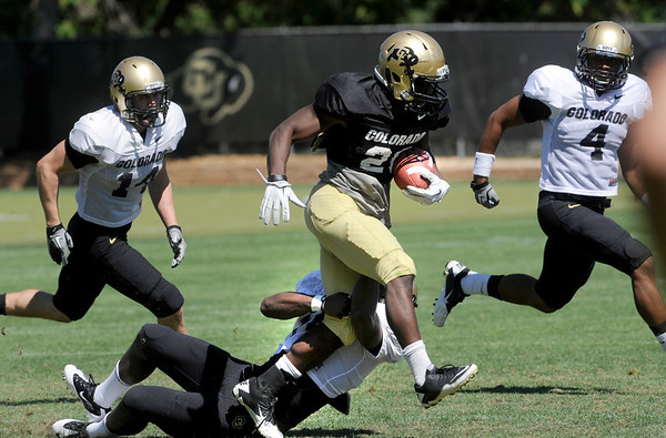 "Brian Lockridge, 20, runs over a defender as Kyle Washington, 4, looks to cut him off during the University of Colorado football team practice on Monday.<br /> Photo by Paul Aiken  August 8, 2011.<br /> FOR MORE PHOTOS AND VIDEO INTERVIEWS FROM THE PRACTICE GO TO  <a href=""http://WWW.DAILYCAMERA.COM"">http://WWW.DAILYCAMERA.COM</a> OR BUFFZONE.COM"