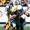 University of Colorado Buffalo's Brian Lockridge (20) is tackled by University of Wyoming Cowboy's Brian Hendricks (8) and Marcell Gipson (2) during their game at Folsom Field in Boulder, Colorado on Saturday, Sept. 19, 2009.<br /> KASIA BROUSSALIAN / THE CAMERA