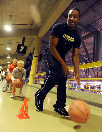 """Shannon Sharpe helps Bryce, left, and Brett McGuffin with dribbling skills during the festival.<br /> The University of Colorado basketball programs  held the CU Basketball Tip-Off  Festival on Sunday. For more photos, go to  <a href=""""http://www.dailycamera.com"""">http://www.dailycamera.com</a>.<br /> Cliff Grassmick / November 7, 2010"""