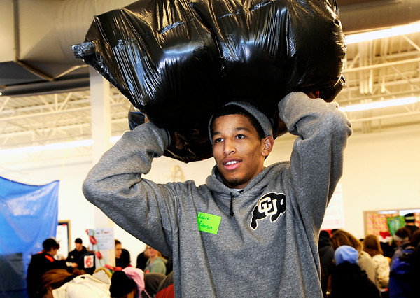 "University of Colorado's Andre Roberson carries a bag full of presents to a clients car while volunteering for the Share-A-Gift organization on Saturday, Dec. 17, at 4601 Nautilus Court in Boulder. For more photos and video  of the event go to  <a href=""http://www.dailycamera.com"">http://www.dailycamera.com</a><br /> Jeremy Papasso/ Camera"