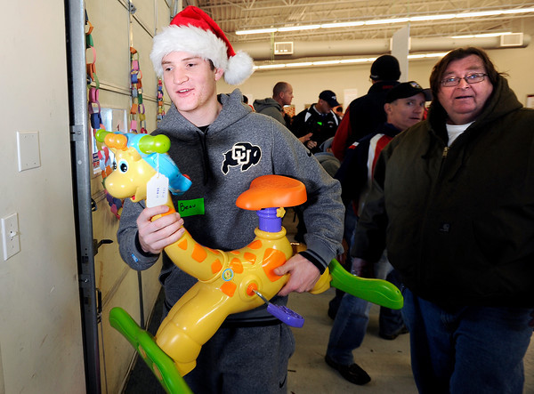 "University of Colorado's Beau Gamble, left, carries a toy for Richy Graham, of Boulder, right, while volunteering for the Share-A-Gift organization on Saturday, Dec. 17, at 4601 Nautilus Court in Boulder. For more photos and video  of the event go to  <a href=""http://www.dailycamera.com"">http://www.dailycamera.com</a><br /> Jeremy Papasso/ Camera"