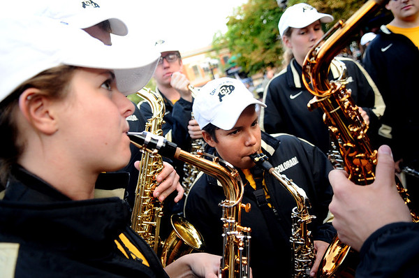 University of Colorado junior Dani Ramos, middle, and sophomore Sammy Verrill, at left, play their saxophones together during the Stampede on Friday, Sept. 16, on the Pearl Street Mall in Boulder. The group were part of the University of Colorado's marching band.<br /> Jeremy Papasso/ Camera