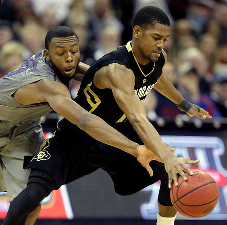 Kansas State guard Jacob Pullen, left, attempts to steal the ball from Colorado guard Cory Higgins during the second half of an NCAA college basketball game in the Big 12 Men's Basketball tournament Thursday, March 10, 2011 in Kansas City, Mo. Colorado won the game 87-75. (AP Photo/Charlie Riedel)