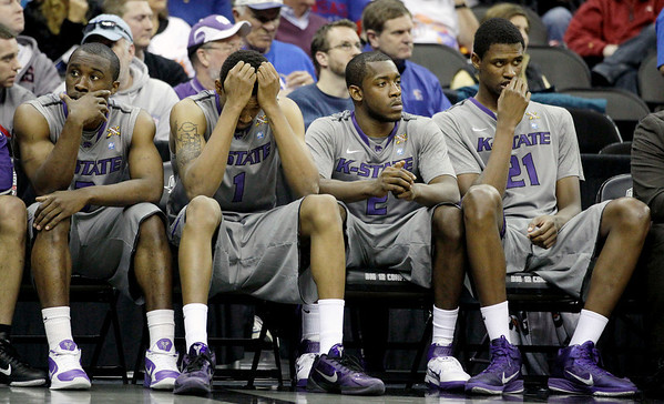 Kansas State players Martavious Irving, left, Shane Southwell (1), Devon Peterson (2) and Jordan Henriquez-Roberts (21) sit on the bench in the final moments of an NCAA college basketball game against Colorado in the Big 12 Men's Basketball tournament Thursday, March 10, 2011 in Kansas City, Mo. Colorado won the game 87-75. (AP Photo/Charlie Riedel)