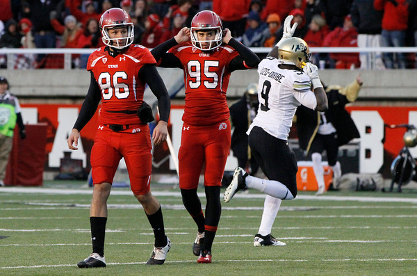 Utah holder Sean Sellwood (86) and kicker Coleman Petersen (95) walk off the field as Colorado defensive end Chidera Uzo-Diribe (9) celebrates after Petersen missed a potential game-tying field goal during the second half of an NCAA college football game, Friday, Nov. 25, 2011, in Salt Lake City. Colorado won 17-14. (AP Photo/Jim Urquhart)