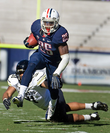 Arizona's Ka'Deem Carey (25) outruns an attempted tackle by Colorado's Kirk Poston (91) during the first half of an NCAA college football game at Arizona Stadium in Tucson, Ariz., Saturday, Nov. 10, 2012. Arizona won 56 -31. (AP Photo/Wily Low)