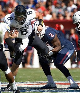 Colorado starting quarterback Nick Hirschman (8) is held up by Arizona's Marquis Flowers (2) for lost yardage during the first half of an NCAA college football game at Arizona Stadium in Tucson, Ariz., Saturday, Nov. 10, 2012. (AP Photo/Wily Low)
