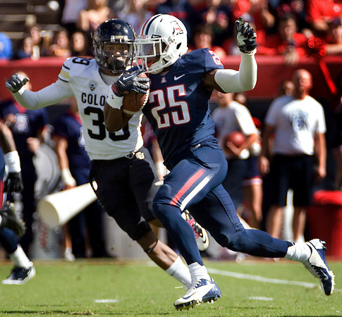 Arizona's Ka'Deem Carey (25) runs ahead of Colorado's Josh Moten (39) for a touchdown during the first half of an NCAA college football game at Arizona Stadium in Tucson, Ariz., Sat., Nov. 10, 2012. (AP Photo/Wily Low)