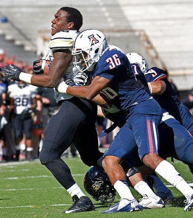 Colorado's Christian Powell, left, loses his helmet as he struggles toward the end zone as Arizona's Vince Miles (36) holds on during the first half of an NCAA college football game at Arizona Stadium in Tucson, Ariz., Saturday, Nov. 10, 2012. (AP Photo/Wily Low)
