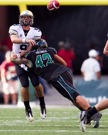 Colorado quarterback Tyler Hansen, left, gets off a pass as Hawaii defensive lineman Paipai Falemalu hits him during the second quarter of an NCAA college football game, Saturday, Sept. 3, 2011, in Honolulu.  (AP Photo/Marco Garcia)