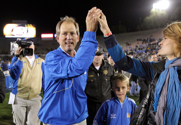 UCLA head coach Rick Neuheisel, left, high-fives with a fan after an NCAA college football game against Colorado, Saturday, Nov. 19, 2011, at the Rose Bowl in Pasadena, Calif. UCLA won 45-6. (AP Photo/Jae Hong)