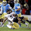Colorado running back Rodney Stewart (5) is tackled by UCLA safety Dalton Hilliard during the first half of an NCAA college football game at the Rose Bowl in Pasadena, Calif., Saturday, Nov. 19, 2011. (AP Photo/Jae Hong)