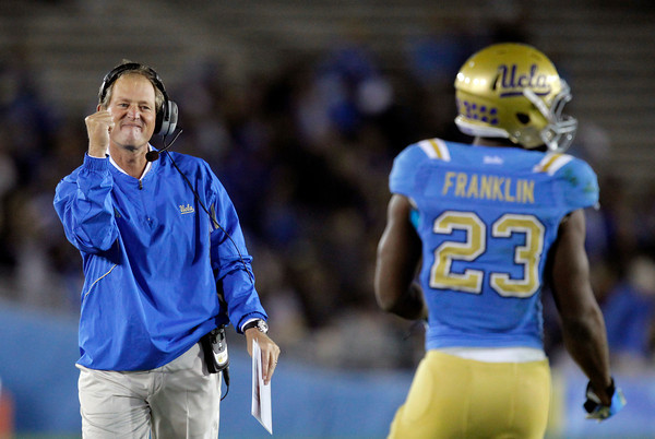 UCLA head coach Rick Neuheisel, left, pumps his fist after Johnathan Franklin, right, scored a touchdown during the first half of an NCAA college football game against Colorado at the Rose Bowl in Pasadena, Calif., Saturday, Nov. 19, 2011. (AP Photo/Jae Hong)