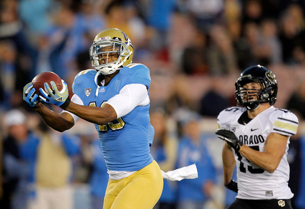 UCLA wide receiver Shaq Evans, left, catches a touchdown pass as he is followed by Colorado's Jason Espinoza during the first half of an NCAA college football game at the Rose Bowl in Pasadena, Calif., Saturday, Nov. 19, 2011. (AP Photo/Jae Hong)