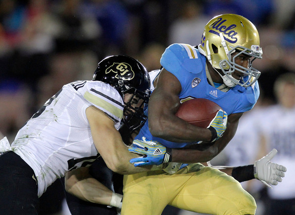 UCLA running back Johnathan Franklin, right, is tackled by Colorado defensive back Travis Sandersfeld during the second half of an NCAA college football game at the Rose Bowl in Pasadena, Calif., Saturday, Nov. 19, 2011. UCLA won 45-6. (AP Photo/Jae Hong)