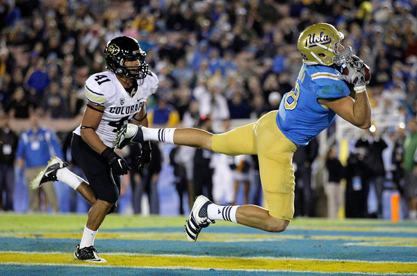 UCLA tight end Joseph Fauria, right, scores a touchdown as he is followed by Colorado defensive back Justin Gorman during the second half of an NCAA college football game at the Rose Bowl in Pasadena, Calif., Saturday, Nov. 19, 2011. UCLA won 45-6. (AP Photo/Jae Hong)