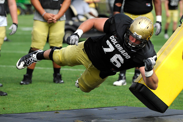 Offensive Lineman Gus Handler, 76, pounds on a tackling dummy during a blocking drill at the University of Colorado football practice on Wednesday morning<br /> Photo by Paul Aiken  August 10, 2011.