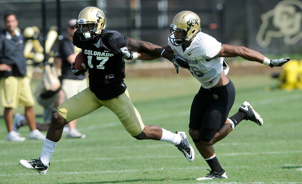 "Wide Receiver Toney Clemons, 17, tries to fend off Defensive Back Ray Polk, 26, during the University of Colorado football practice on Wednesday morning<br /> Photo by Paul Aiken  August 10, 2011.<br /> <br /> FOR MORE PHOTOS AND VIDEO INTERVIEWS FROM PRACTICE GO TO  <a href=""http://WWW.DAILYCAMERA.COM"">http://WWW.DAILYCAMERA.COM</a> AND BUFFZONE. COM"