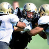 Tight end Kyle Slavin, center, gets hit at the line of scrimmage by Anthony Perkins, 7, and Josh Hartigan, 17 at the University of Colorado football practice on Wednesday morning<br /> Photo by Paul Aiken  August 10, 2011.